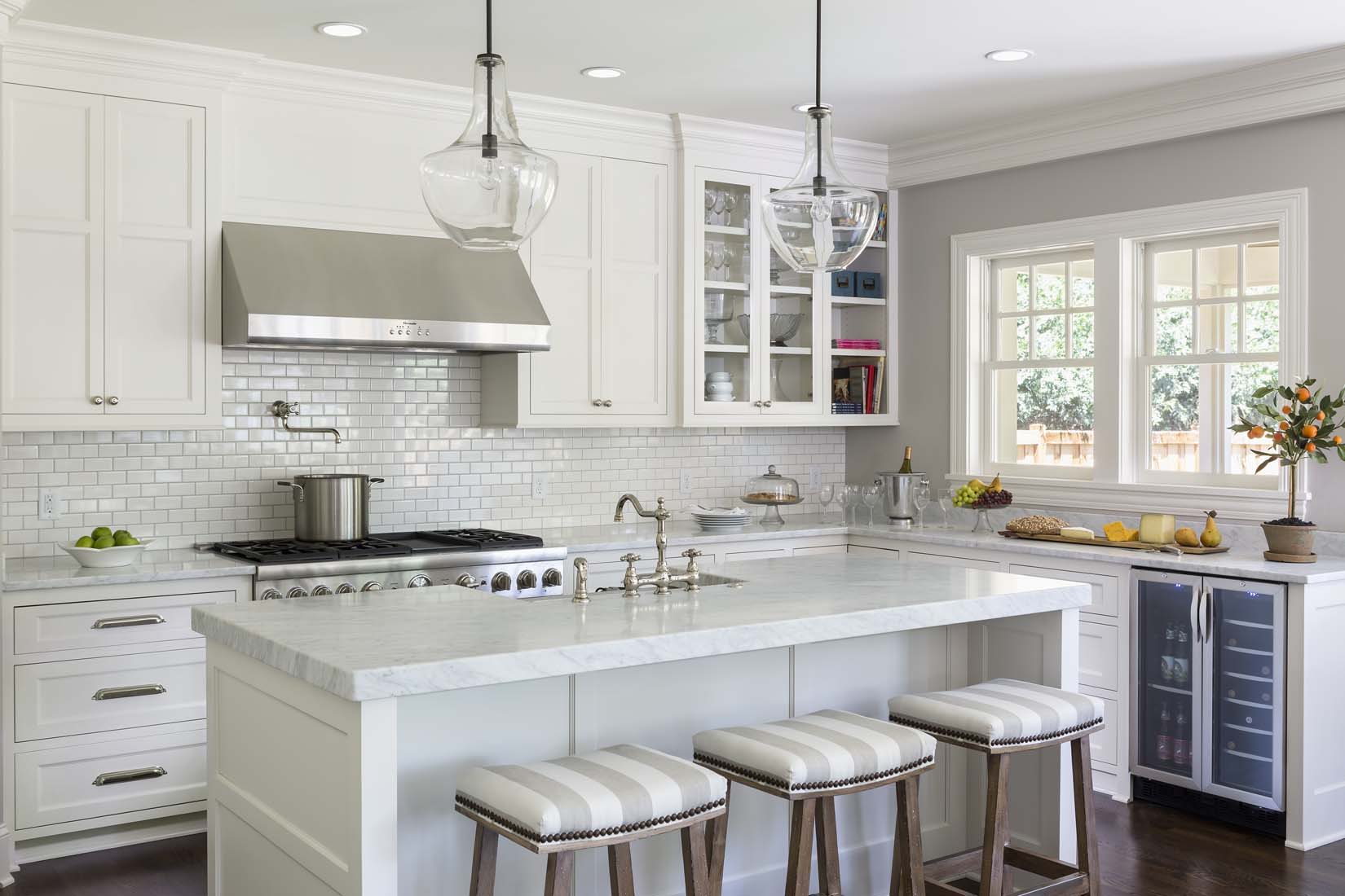 Upscale white kitchen with large island and marble ...