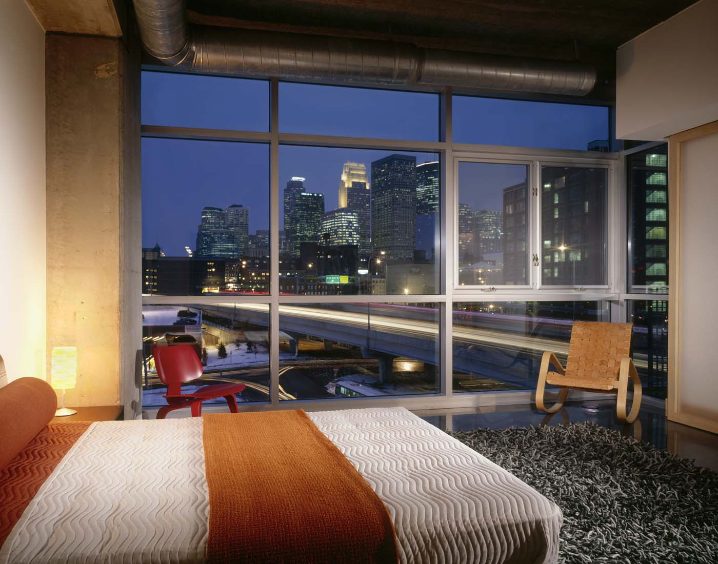 Loft Bedroom At Night With View Of Downtown Buildings